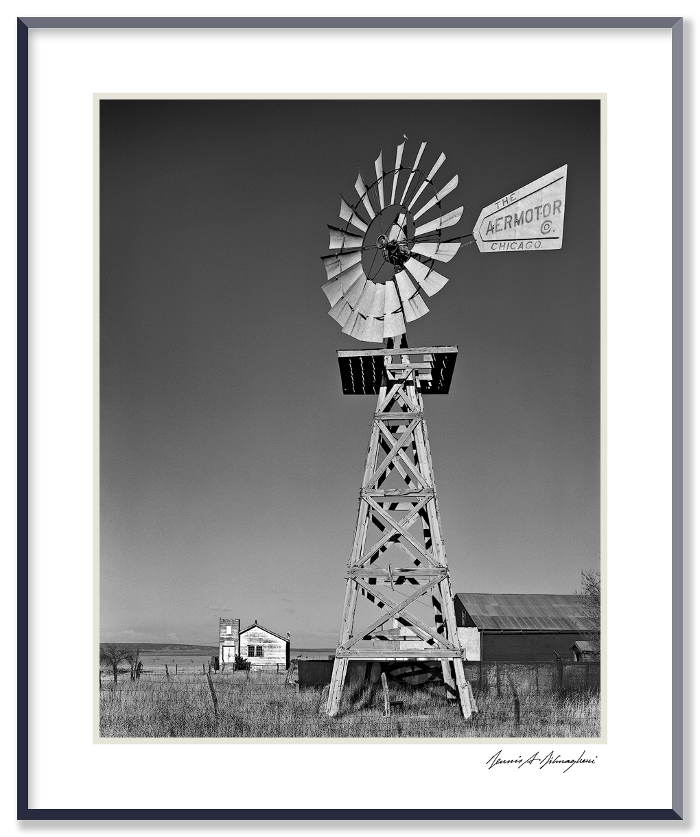 Aermotor Windmill - Claunch, New Mexico, ca. 1976   - Bird's Eye view from atop the windmill blades  Claunch is a near ghost town - a relic of pinto bean farming - yet it survives today. Population 18 in recent census. The Community Church is the white building in the background. The surrounding prairie is windswept and desolate.