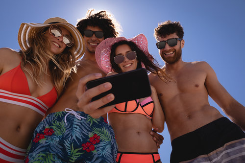 Copy of Group of friends taking selfie with mobile phone at beach in the