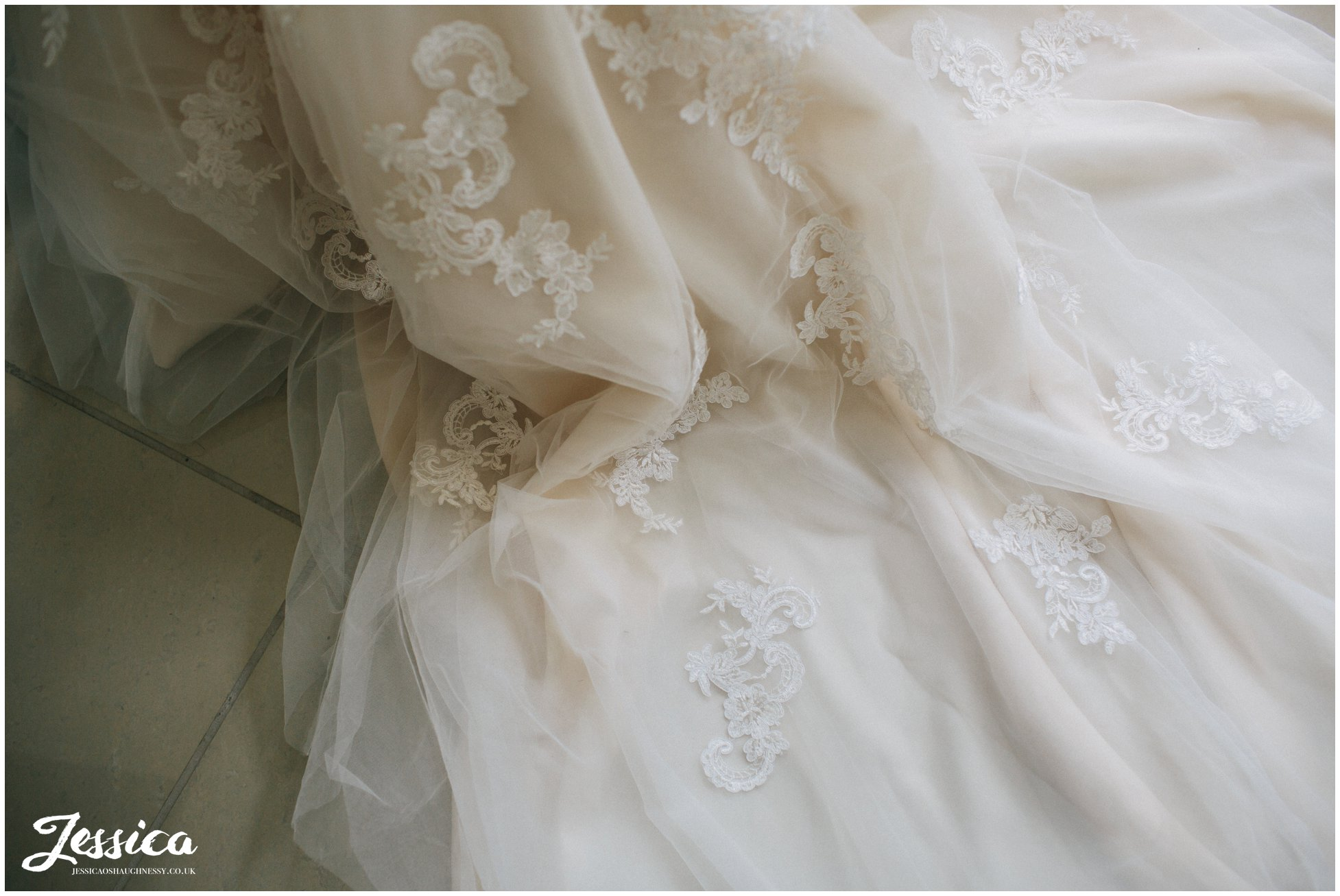 close up of lace detail on the train of the wedding dress