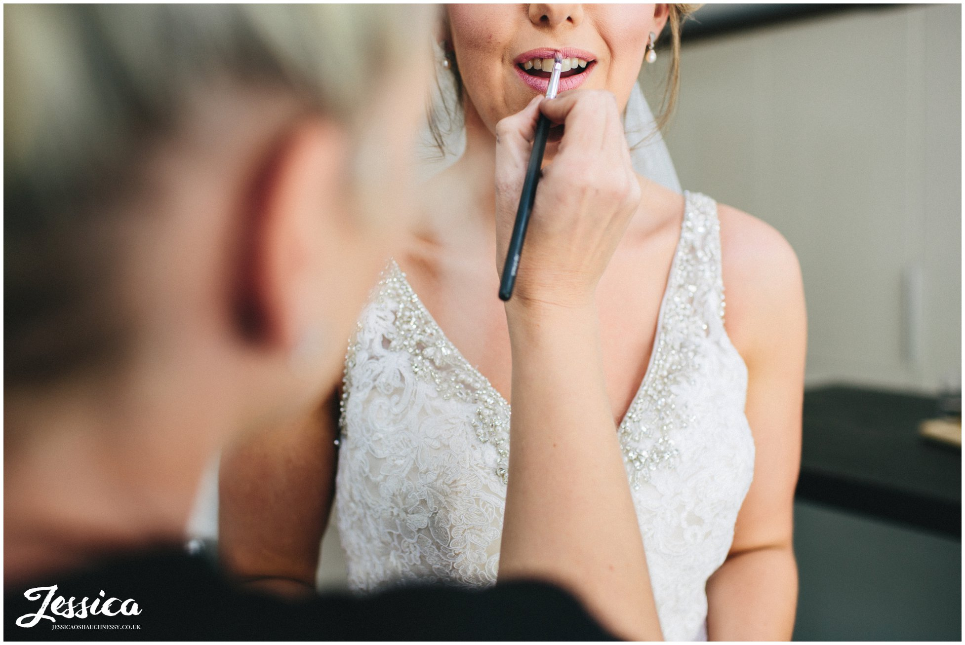the brides lipstick touch ups before leaving for her ceremony at tower hill barns