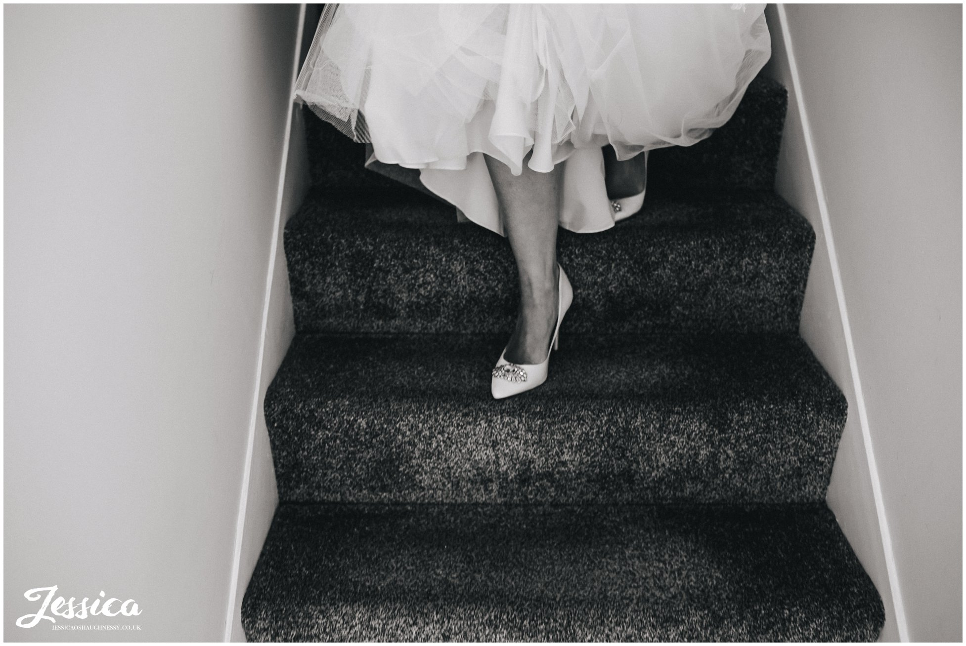 close up of brides feet as she walks down the stairs in her wedding dress