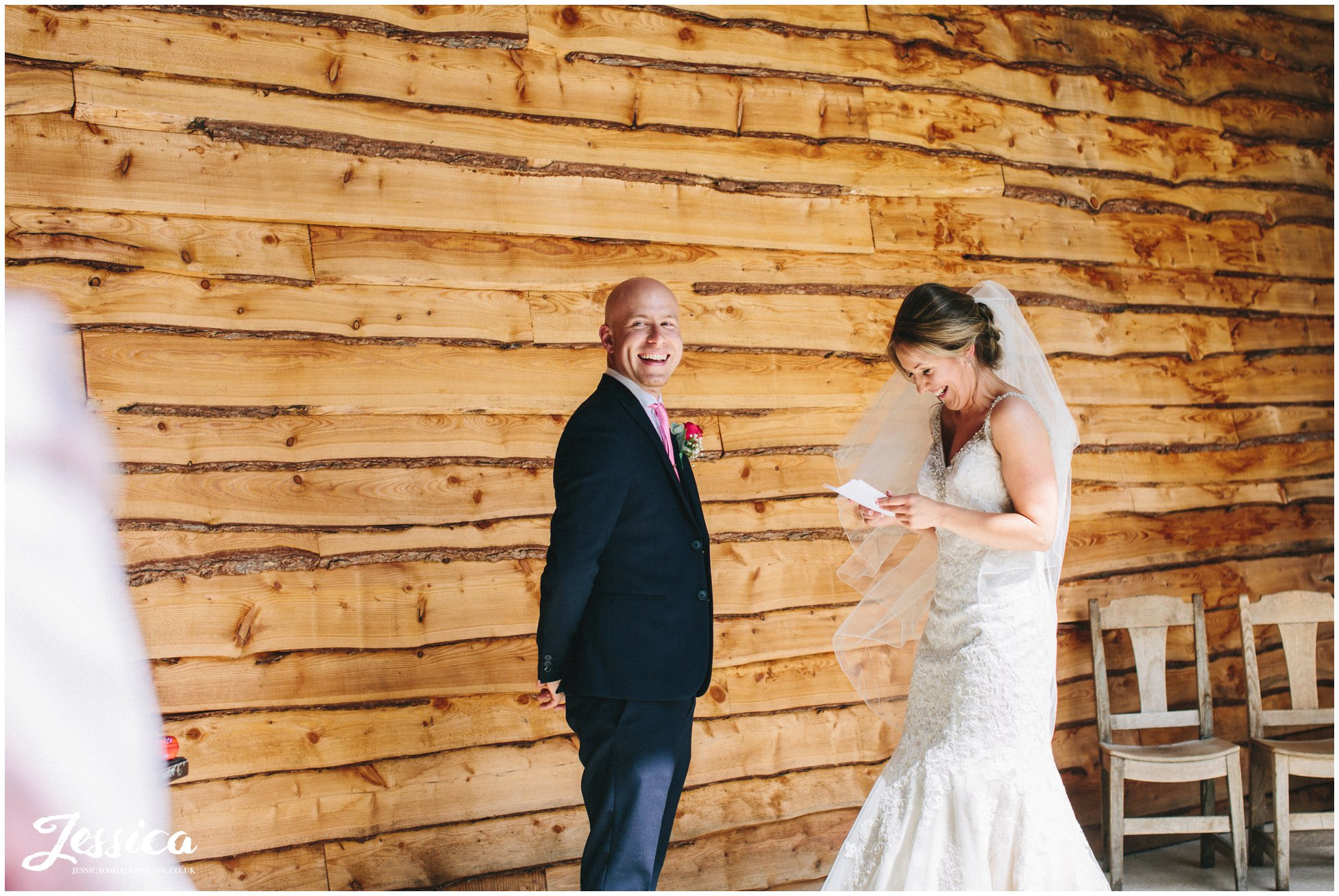 bride & groom laugh whilst they exchange their vows at tower hill barns