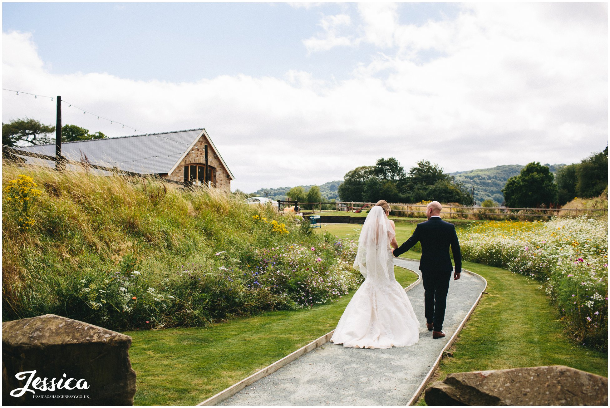 newly wed's walk down path after their wedding ceremony in north wales