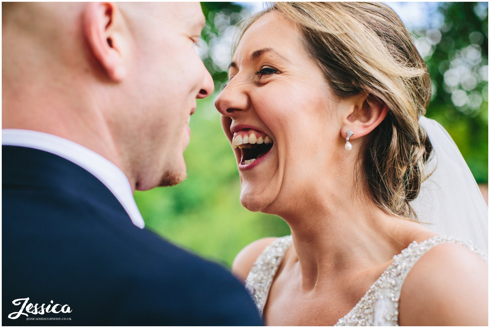 close up of bride and groom laughing at each other on their wedding day in wrexham, north wales