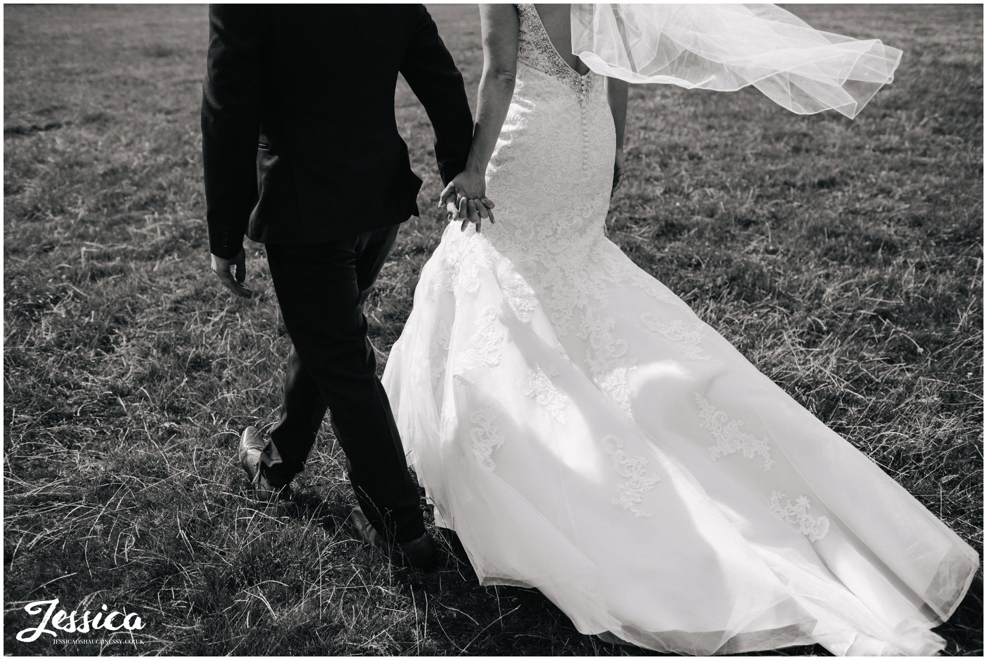 cropped black and white photograph of newly wed's walking through a field in north wales