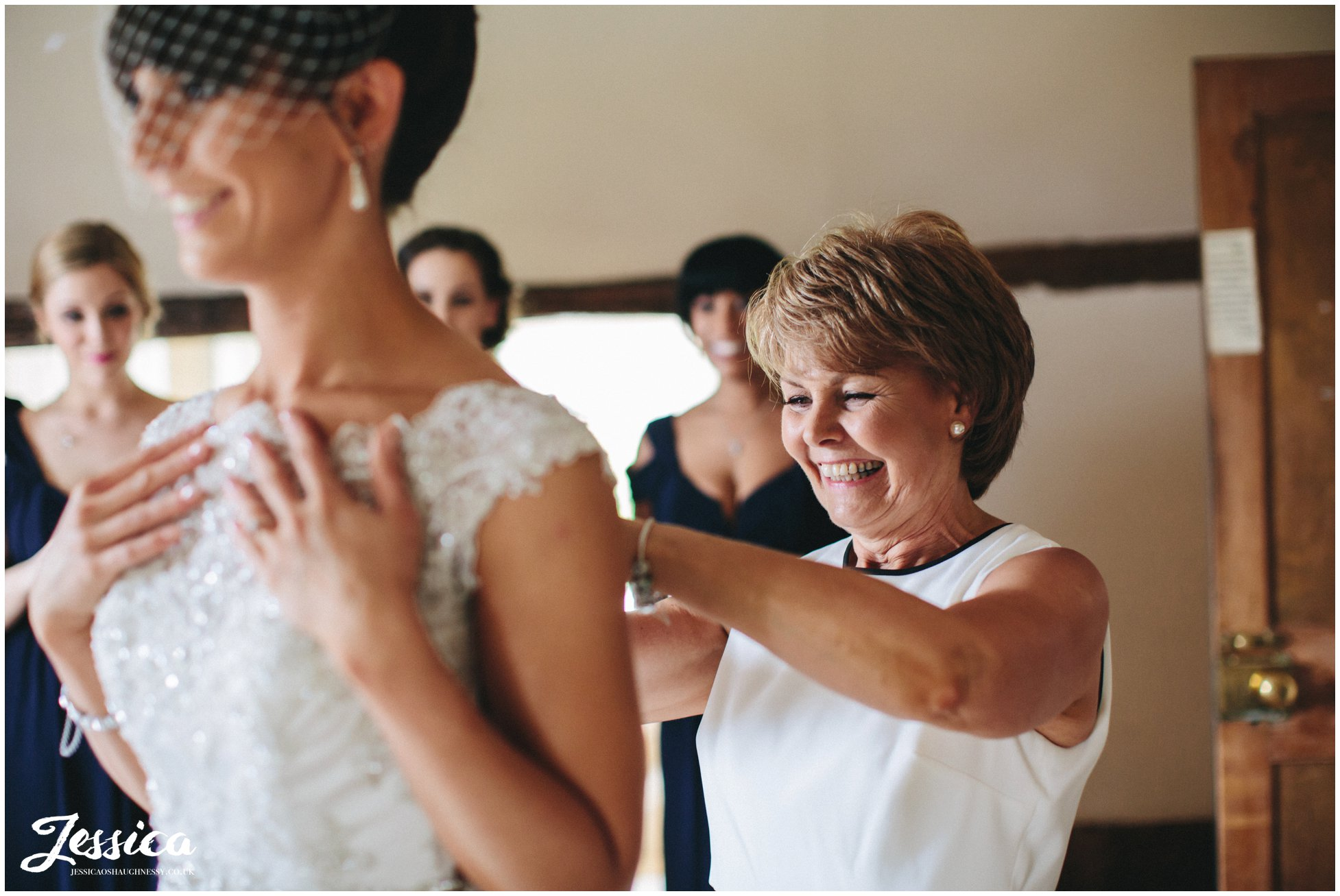 bride helped into her wedding dress by her mother at the mickle trafford manor - chester wedding photographer