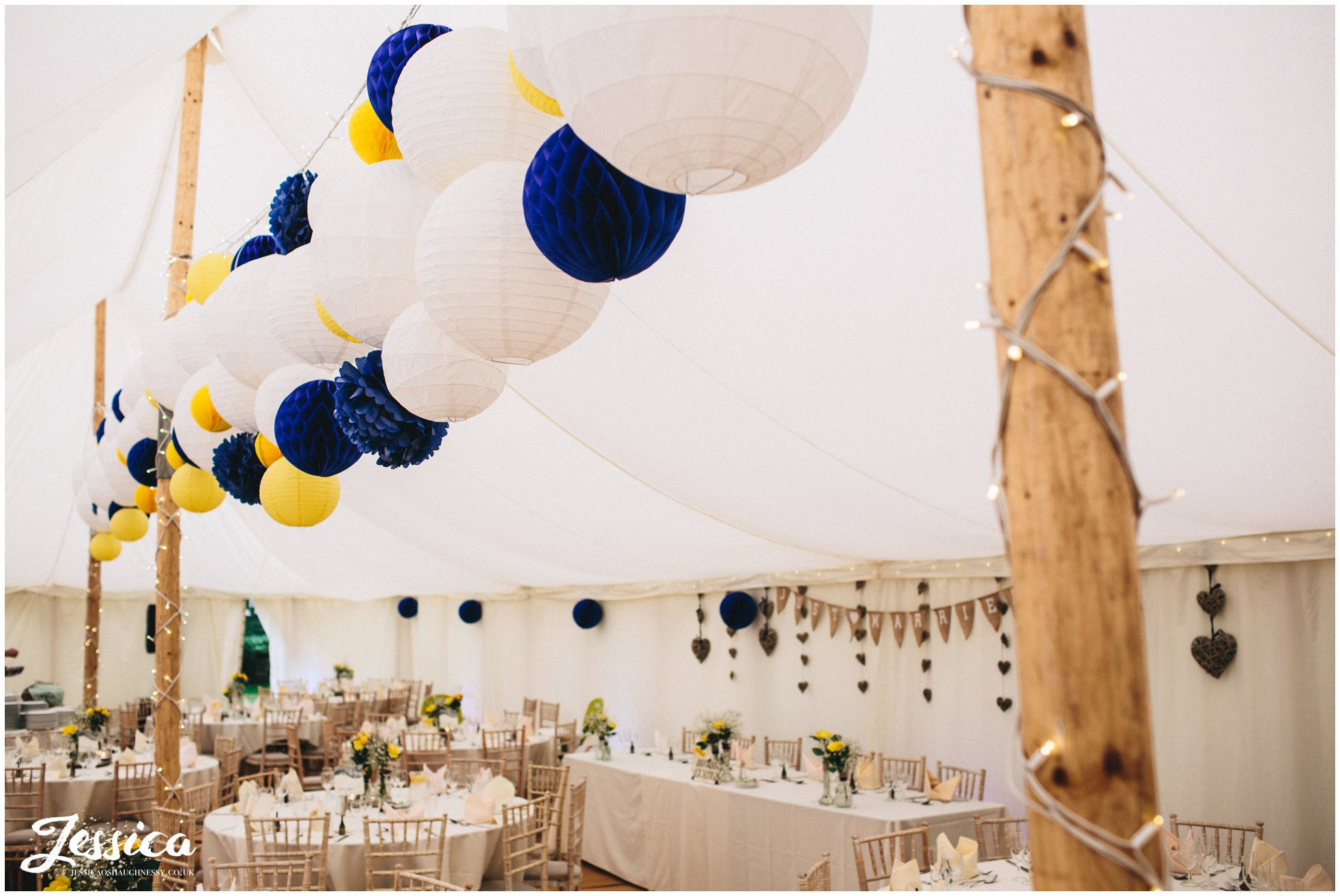blue & yellow lanterns decorate the marquee at a wedding in trafford hall, chester