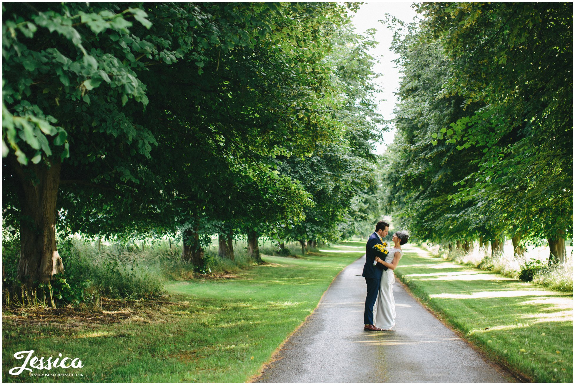 Bride & Groom standing between trees at Trafford Hall, Cheshire wedding photography