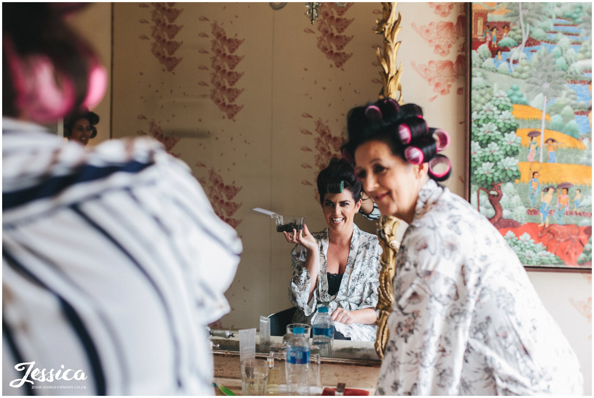 bridesmaid getting her hair done whilst looking into a mirror ready for the wedding in askham hall, lake district