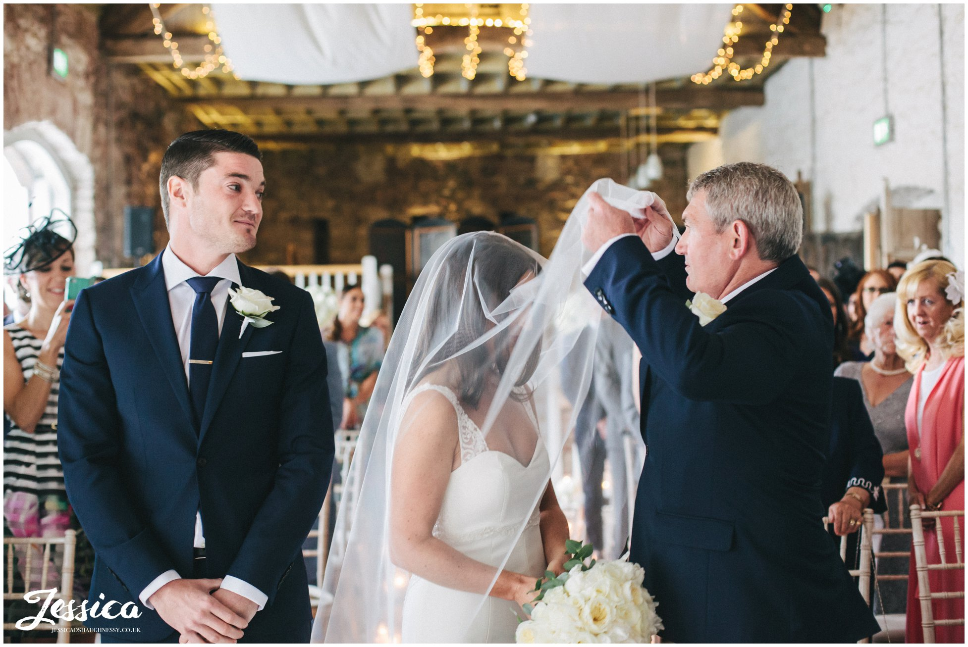 father of the bride lifts brides veil at her askham hall wedding