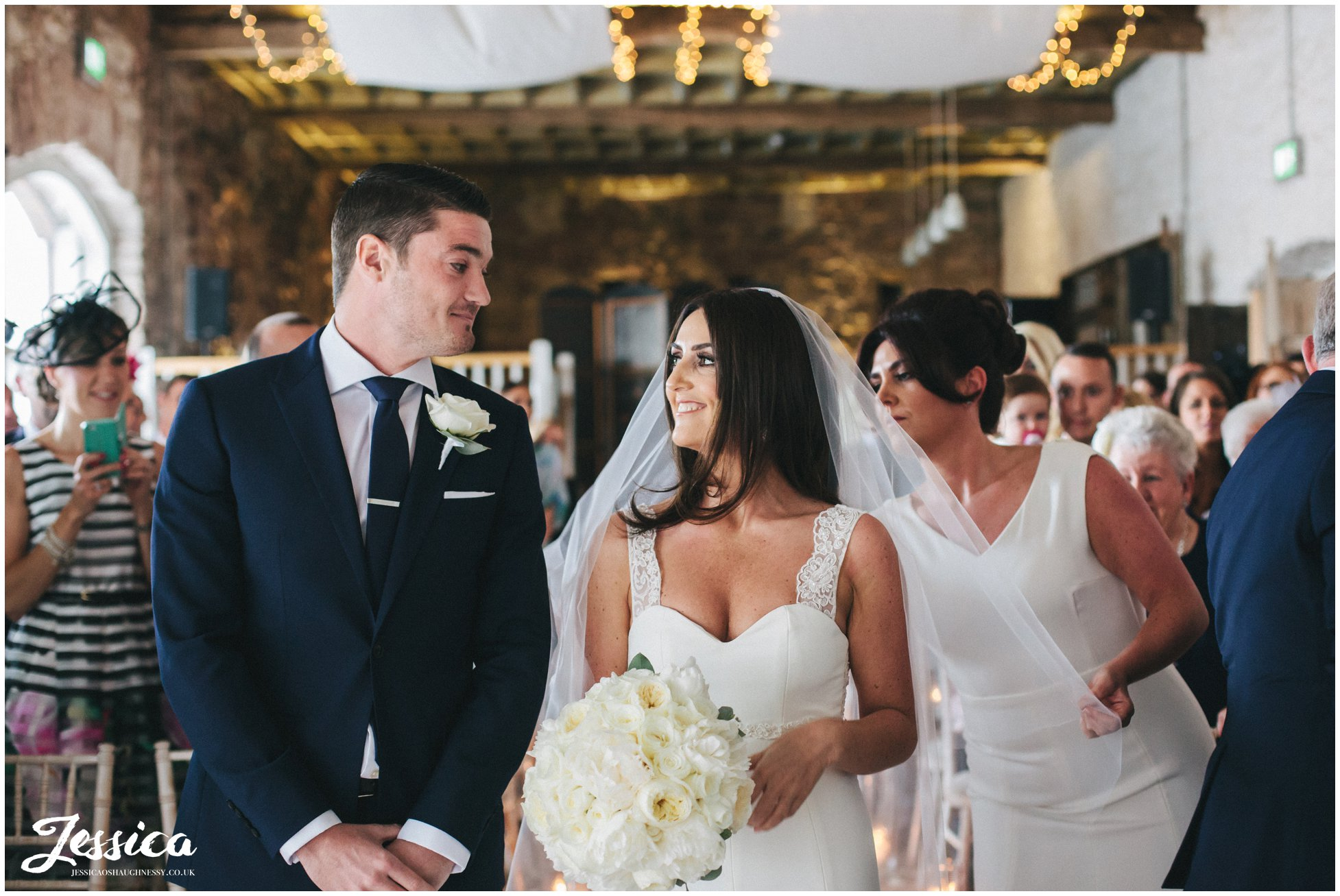bride & groom exchange vows in bank barn, askham hall - lake district wedding photographer