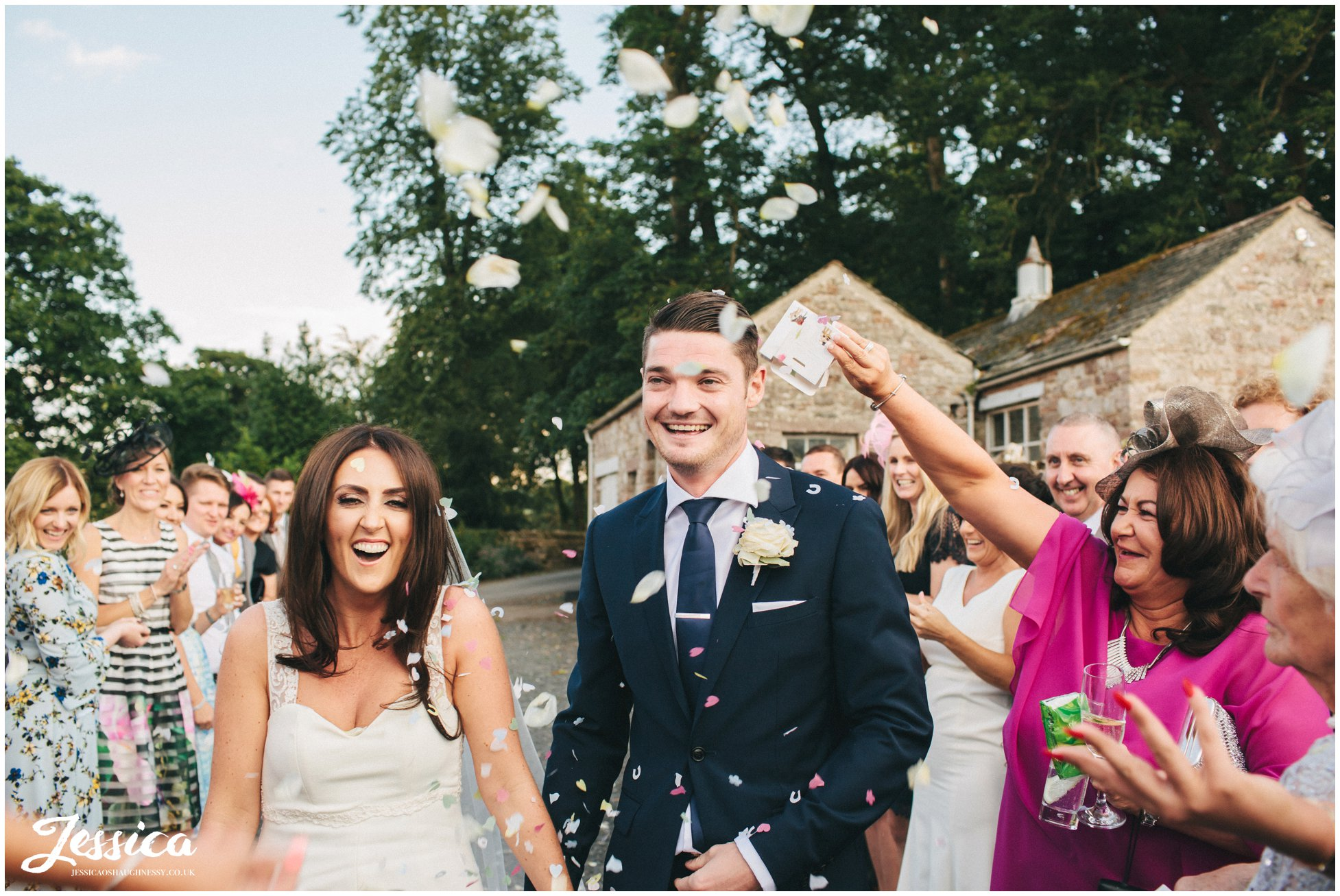 newly wed's walk through confetti line at their lake district wedding