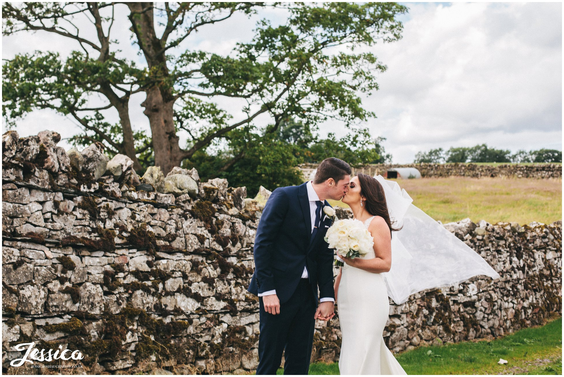 newly wed's share kiss in front of stone wall after their wedding at askham hall in the lake district
