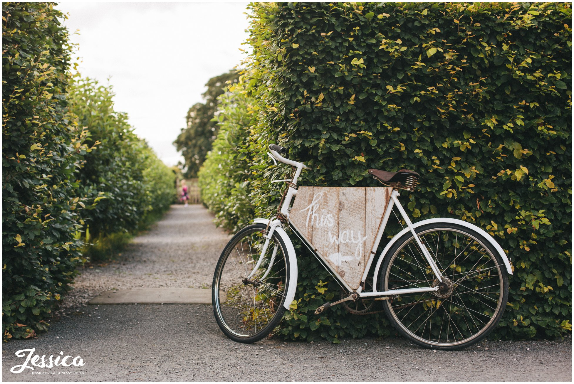 rustic, vintage bike with a 'this way' sign directs wedding guests to bank barn at askham hall