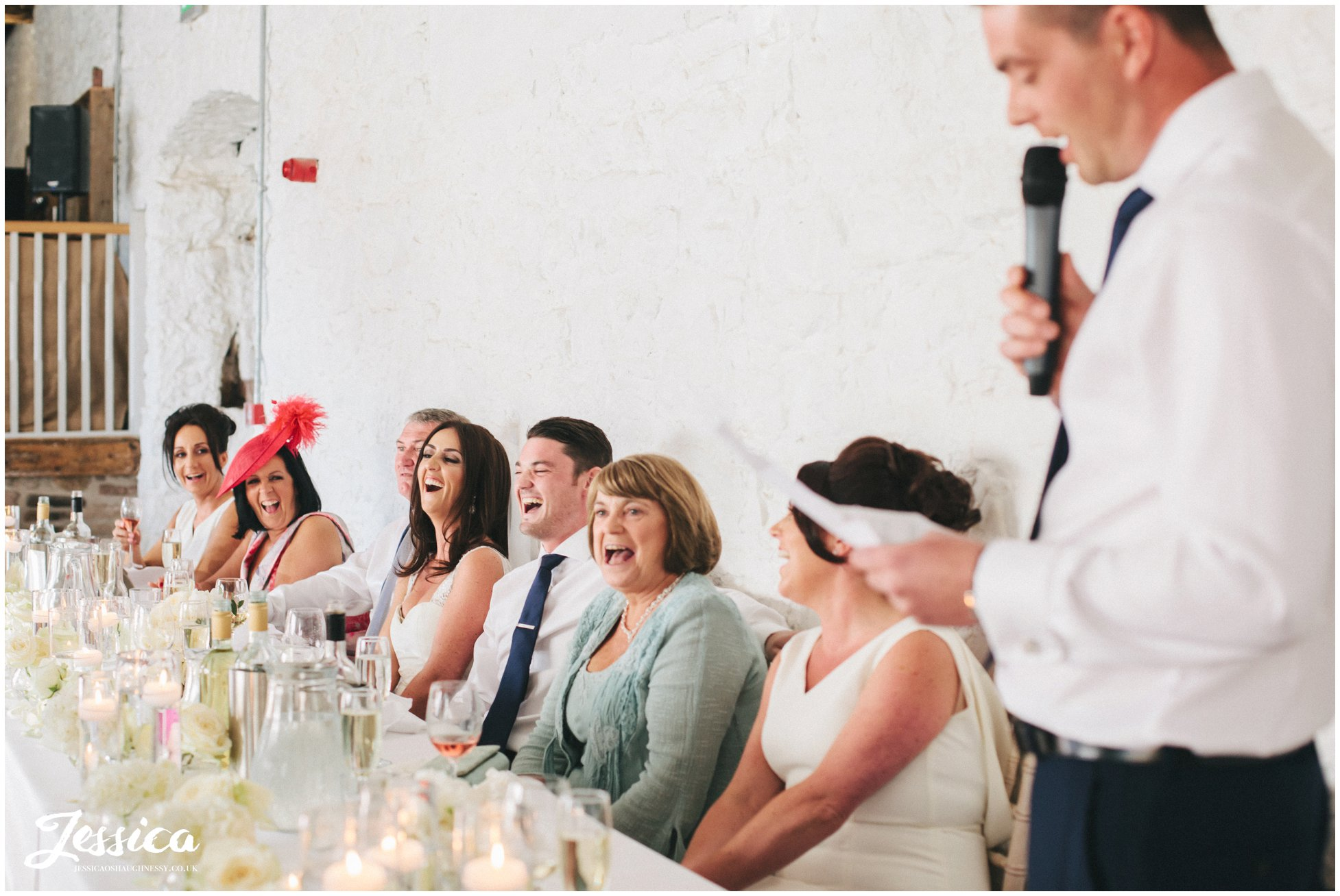 top table laugh at best man's speech at a lake district wedding, penrith