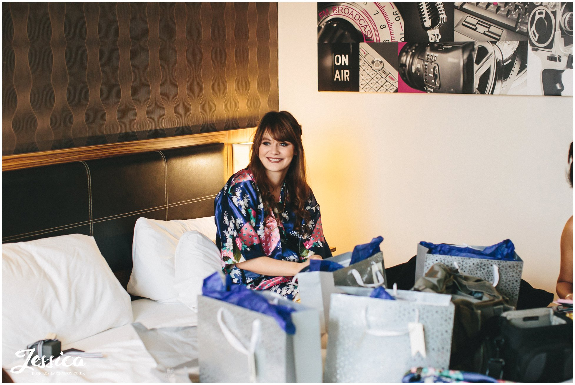 bridesmaid sits on bed laughing in holiday inn, media city