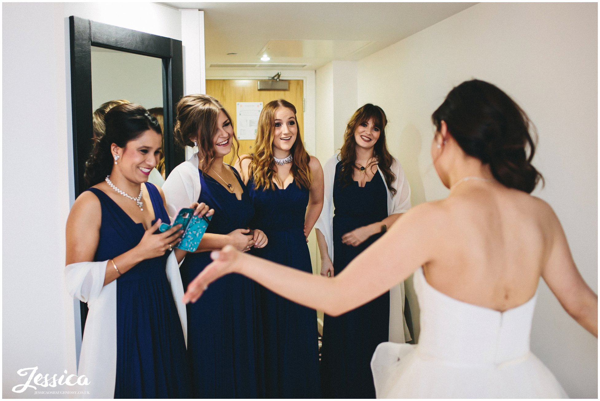 bridesmaids admire the bride & her dress before her wedding ceremony in manchester
