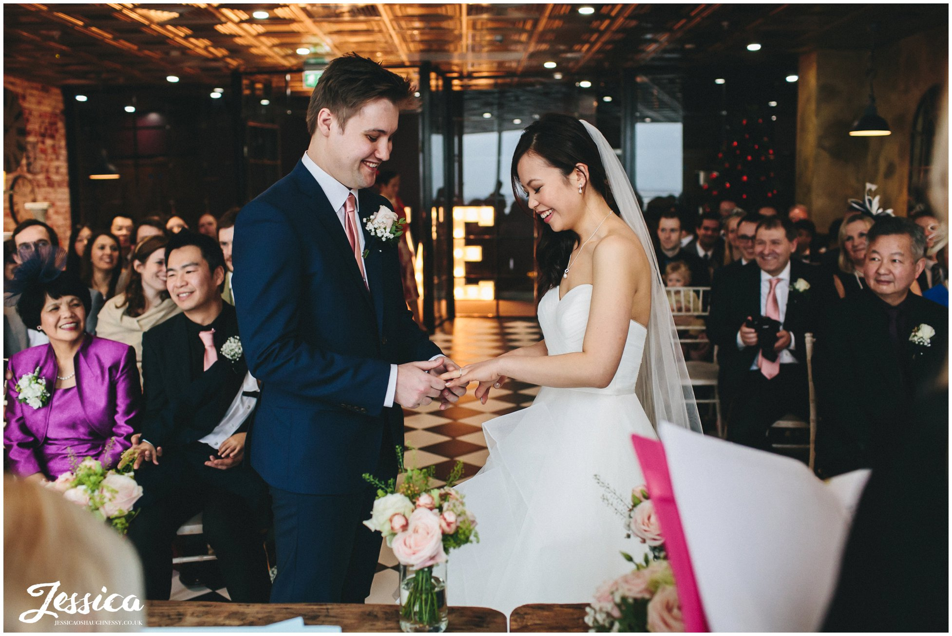 bride & groom exchanging rings - On The 7th Wedding Photography