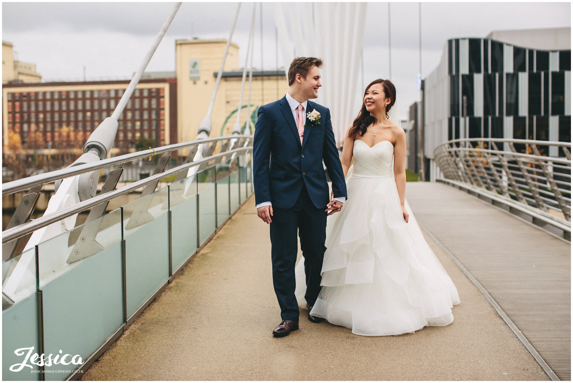 newly weds walk hand in hand over The Media City Footbridge - manchester wedding photographer