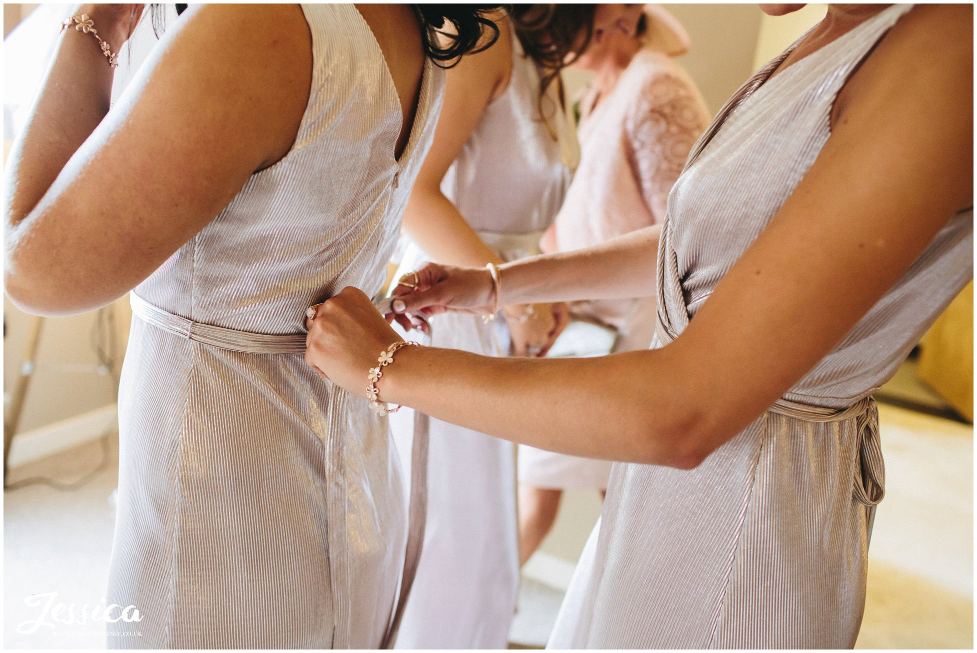 bridesmaids get into their dresses before a wedding at tower hill barns in north wales
