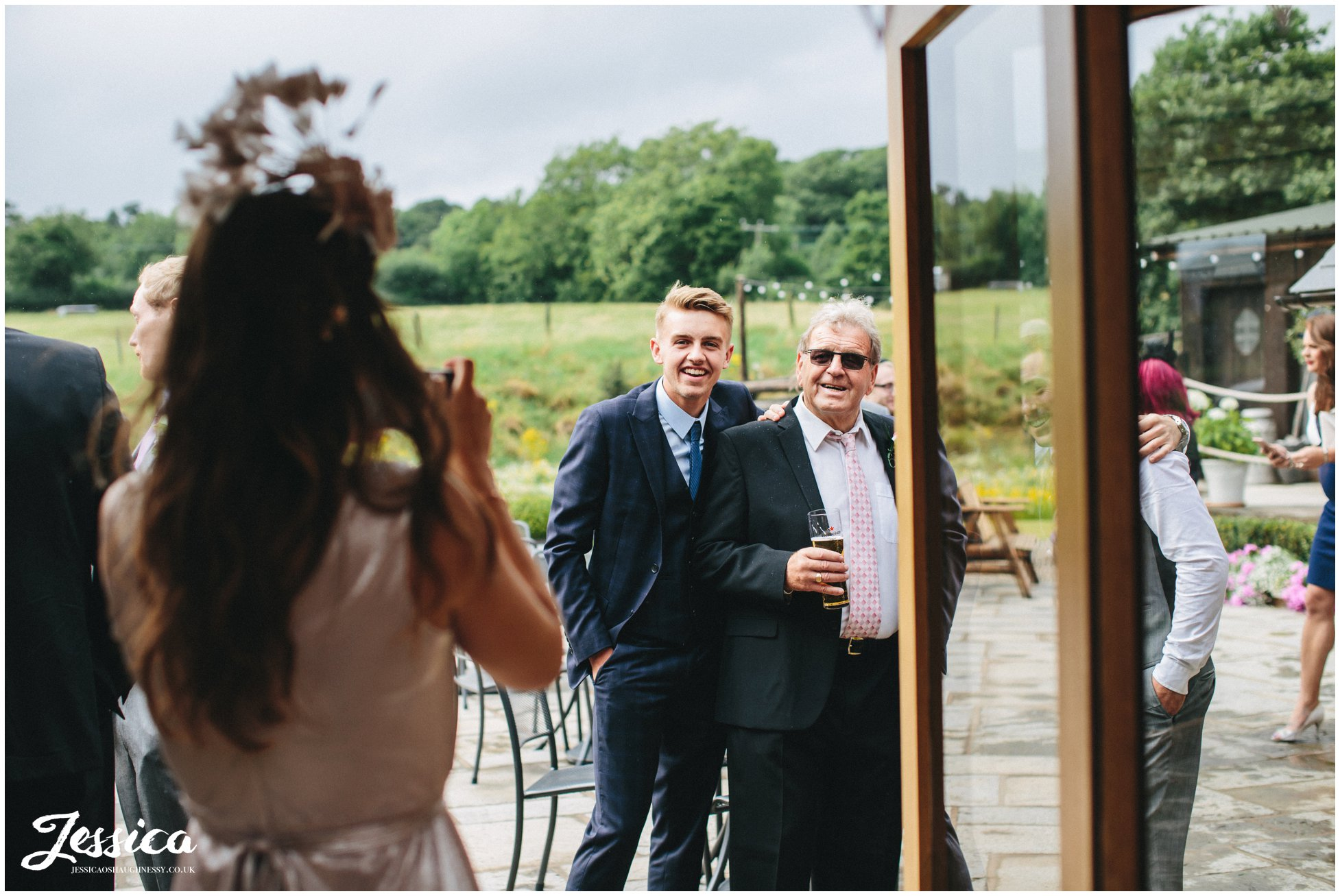 guests pose for photograph stood outside at a north wales wedding