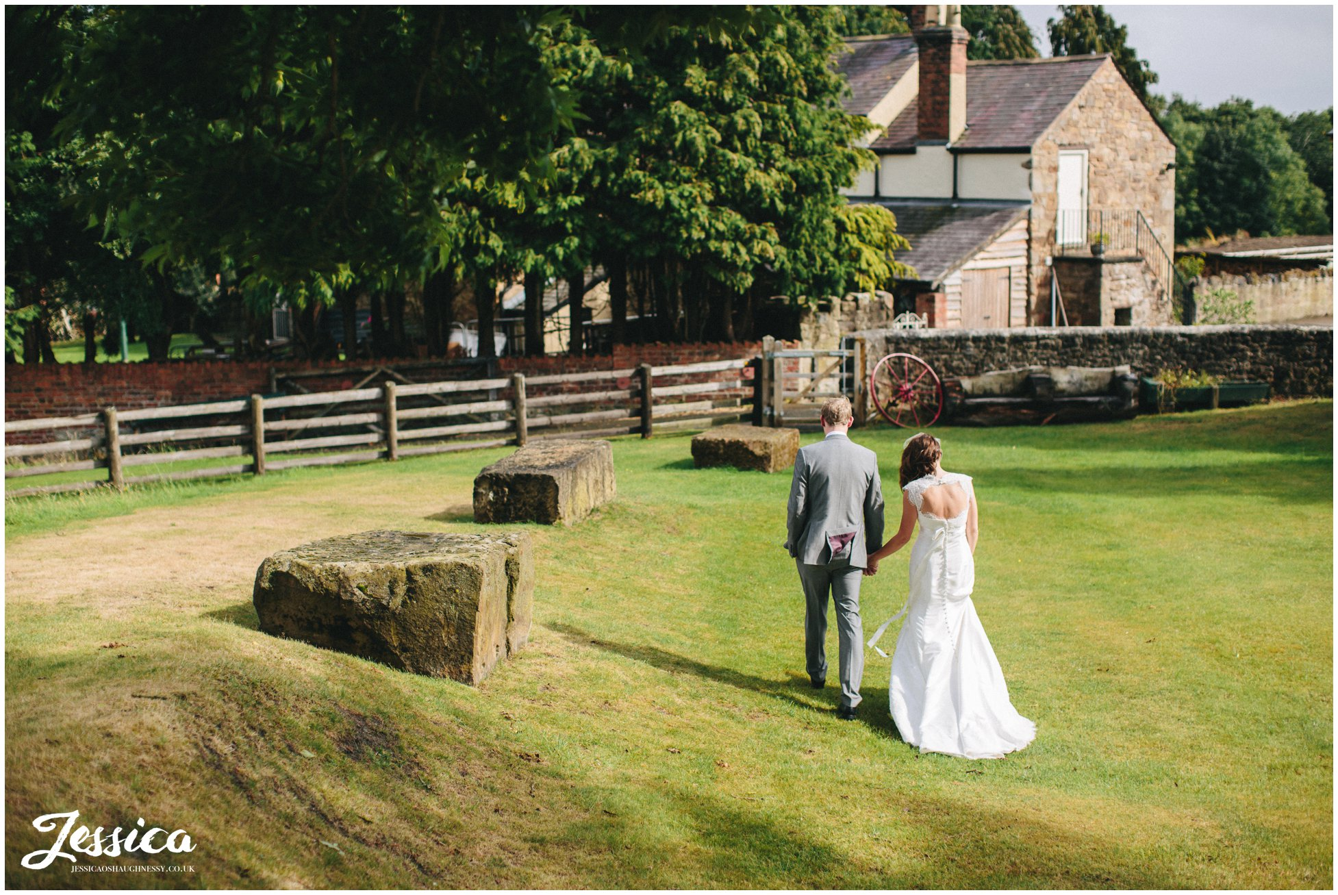 newly wed couple walk hand in hand at tower hill barns in north wales