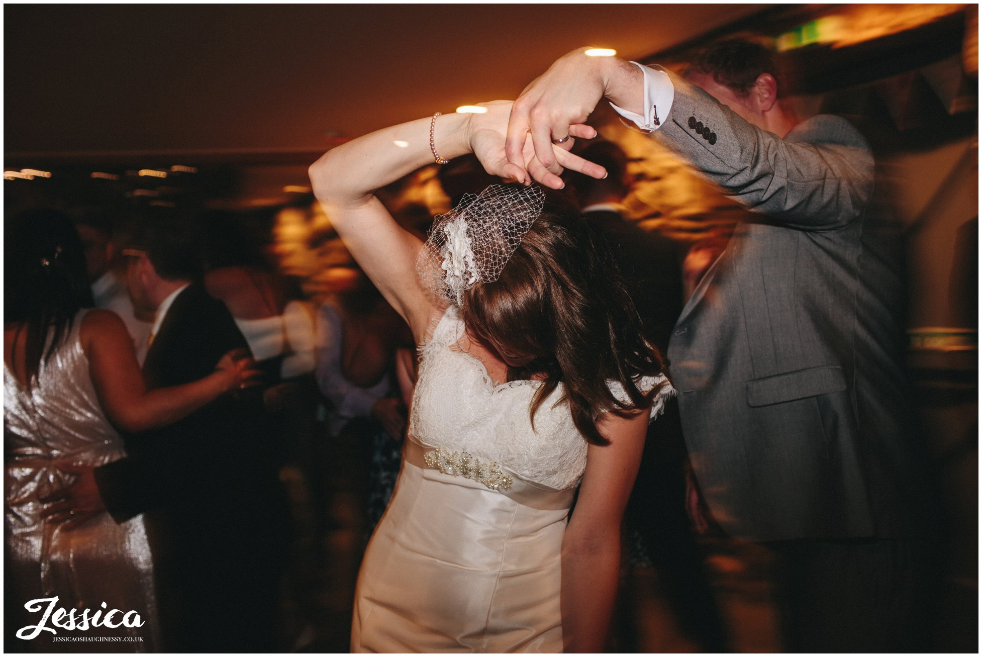 groom spins bride round on the dancefloor