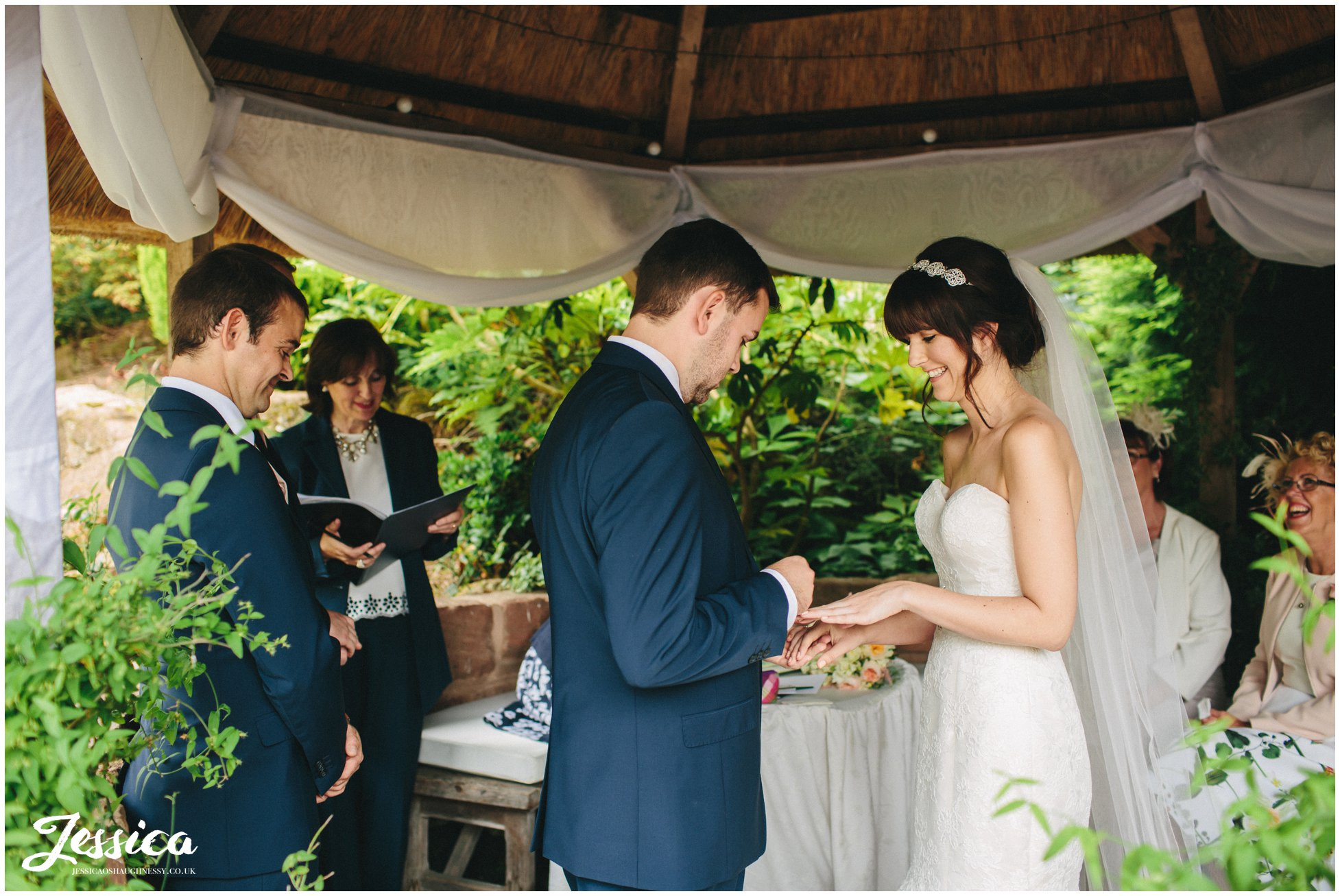 the bride & groom exchange rings at their ness gardens wedding on the wirral