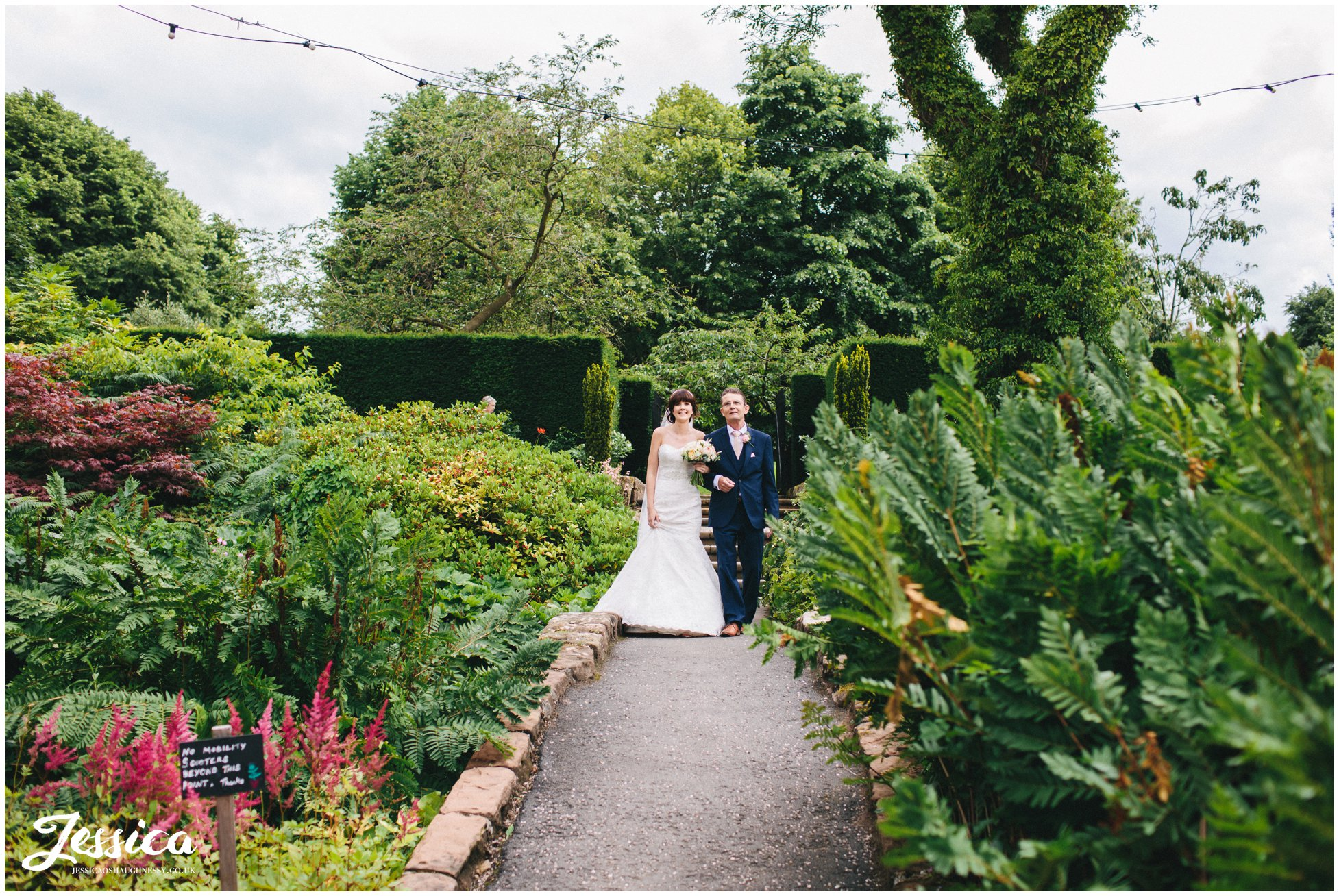 the bride & her father walk down the steps to her wedding ceremony at ness gardens on the wirral