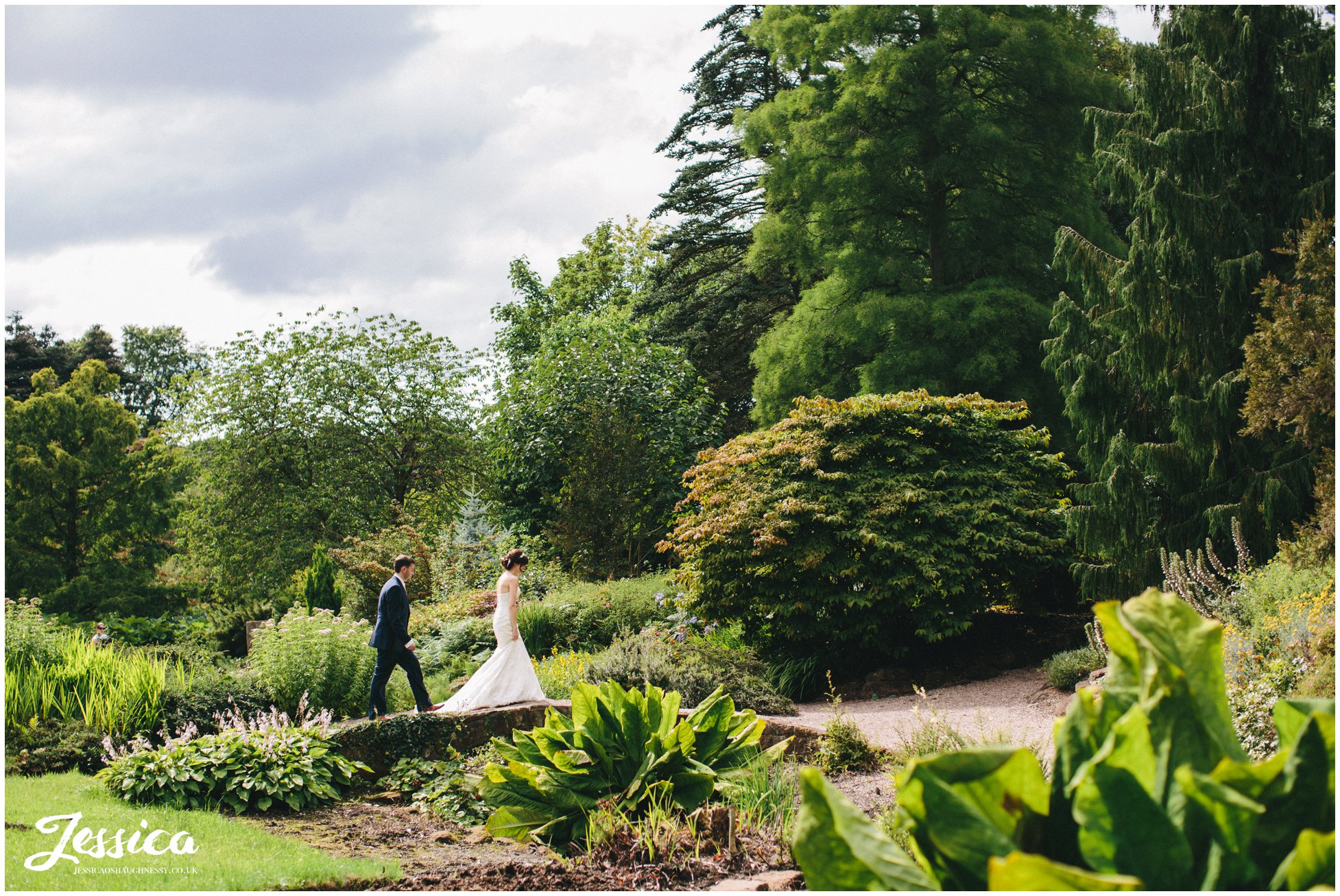 bride & groom walk over a bridge in the distance, ness gardens wedding photographer