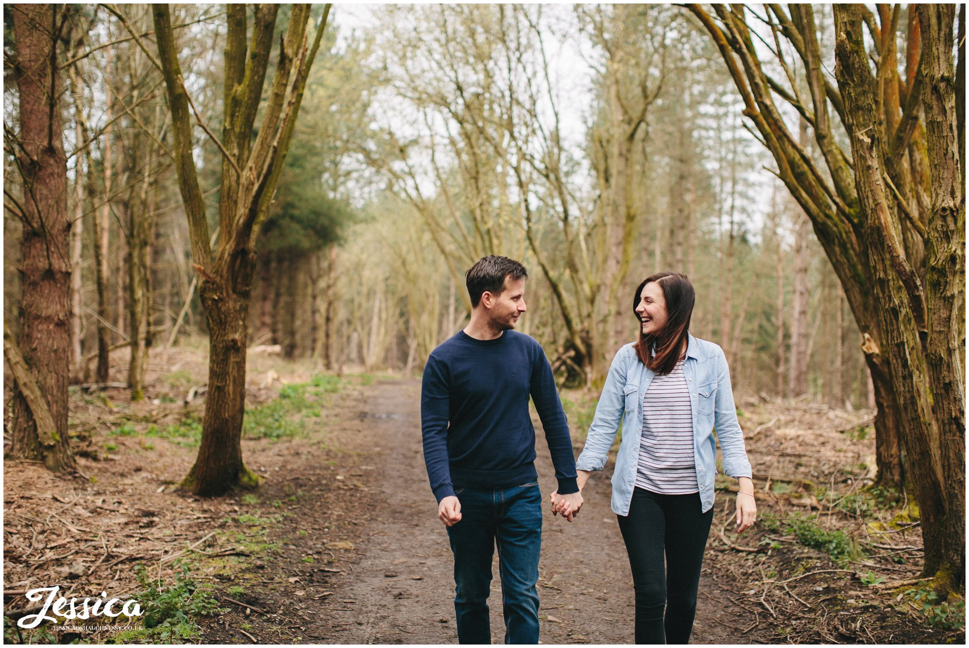 couple walk hand in hand through delamere forest - pre-wedding shoot