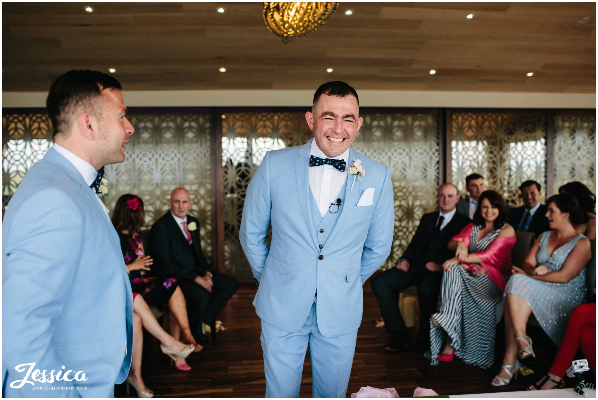 groom smiles as he waits for his bride to walk down the aisle at their sheldrakes wedding