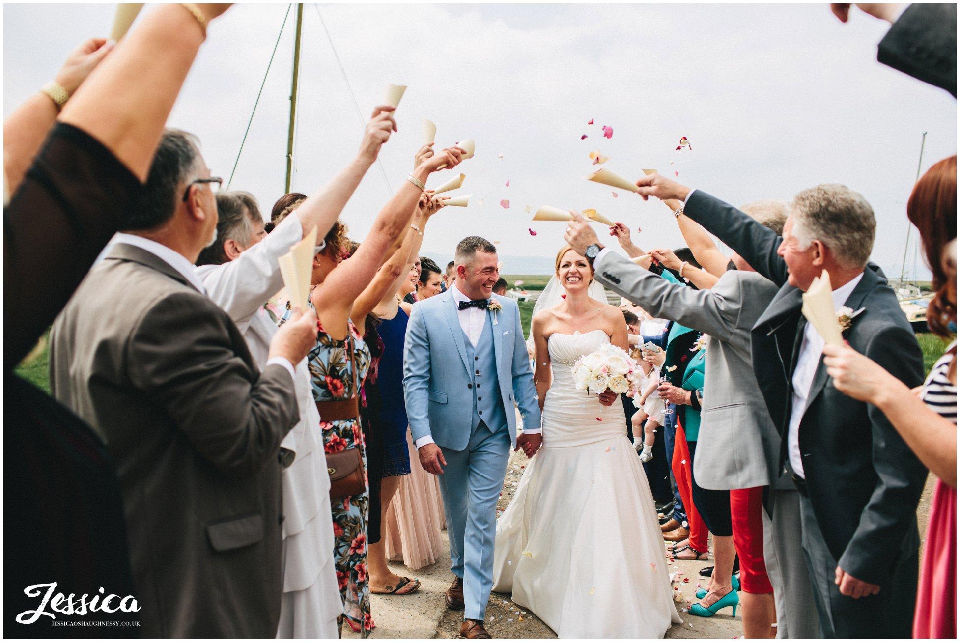 couple walk through the confetti line at their wirral wedding