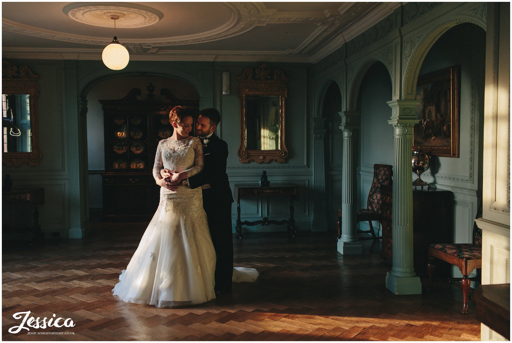interior shot of the bride & groom stood in light pouring through the window at thornton manor