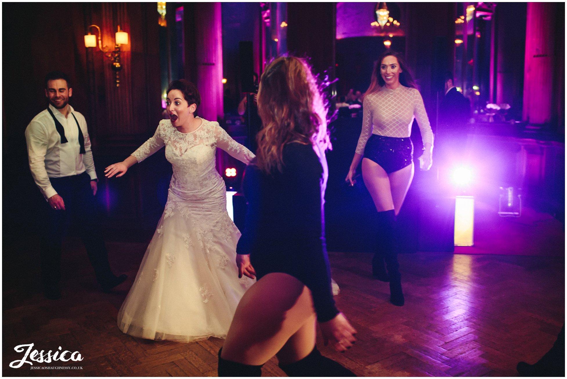 bride looks shocked as her bridesmaid suprises her