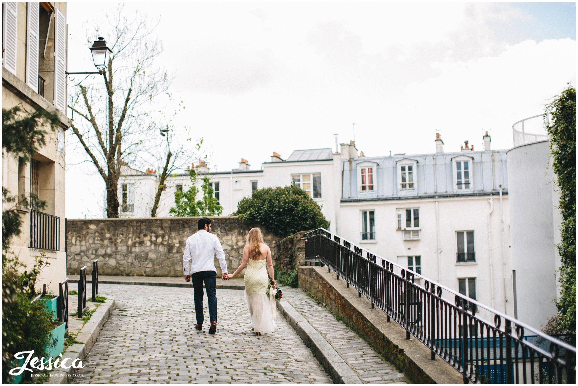 destination wedding photographer - couple hold hands walking down street in mont marte