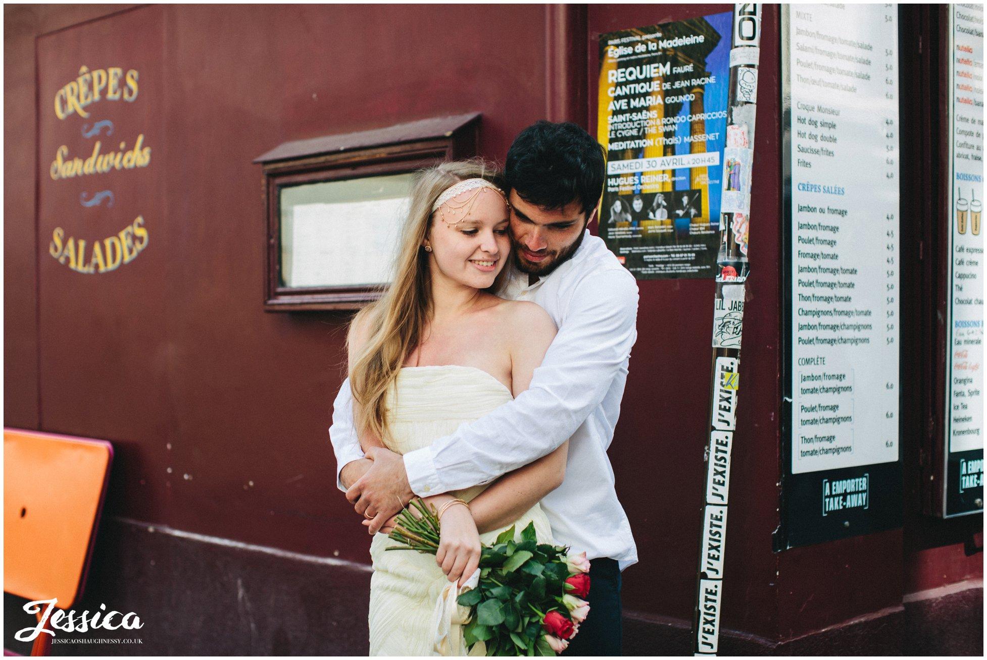 bride & groom embrace on street corner of mont marte in paris