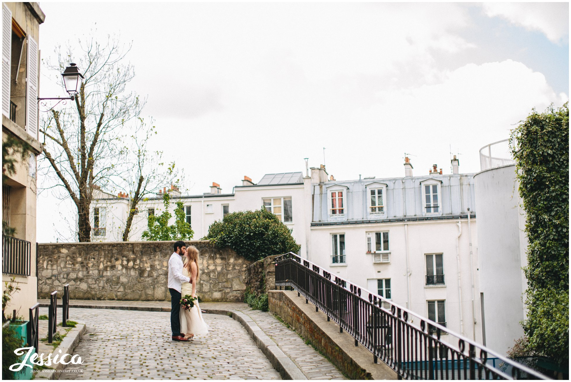 newly weds kiss on parisian street - france wedding photographer