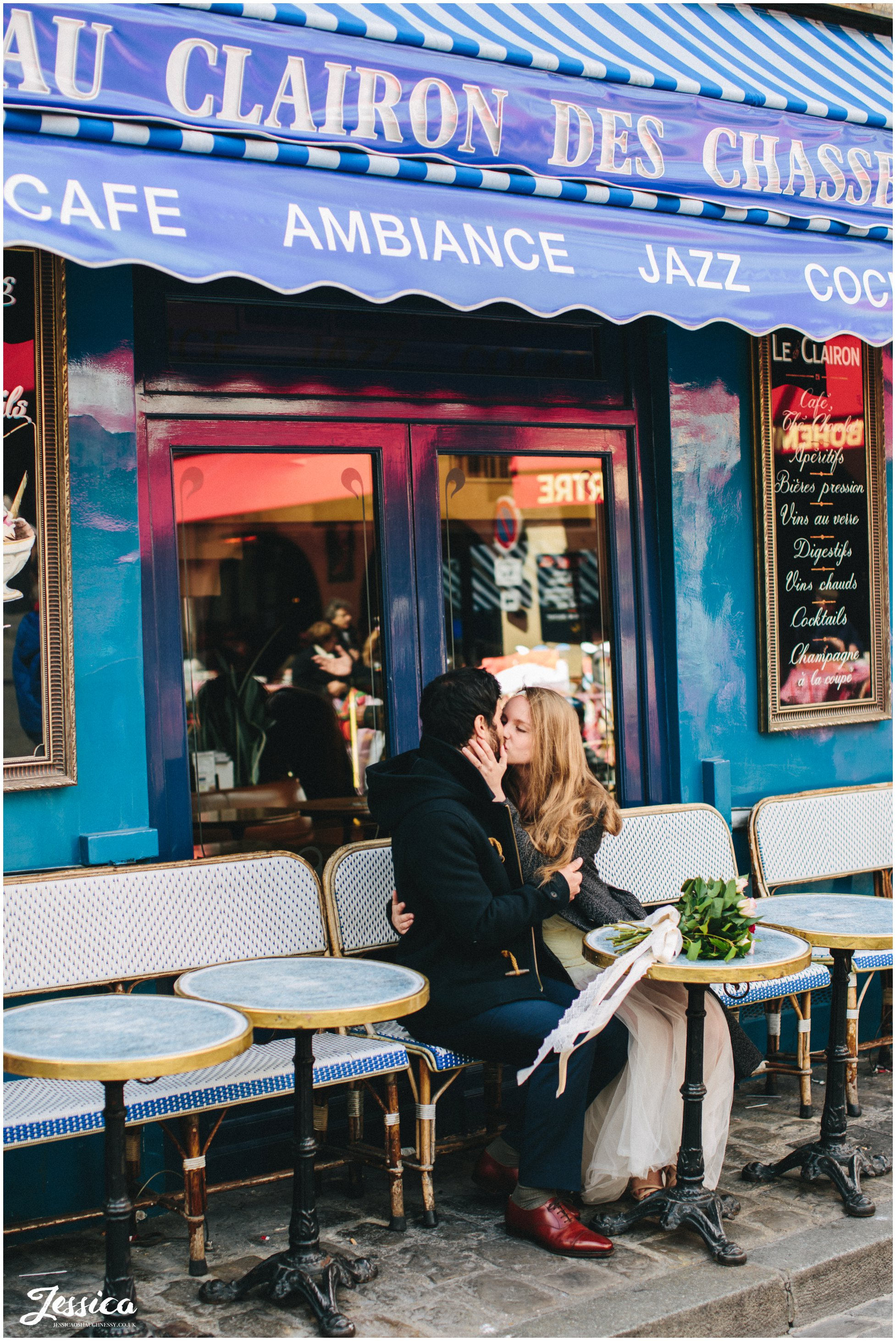 couple sit kissing in front of a blue cafe in mont marte, paris