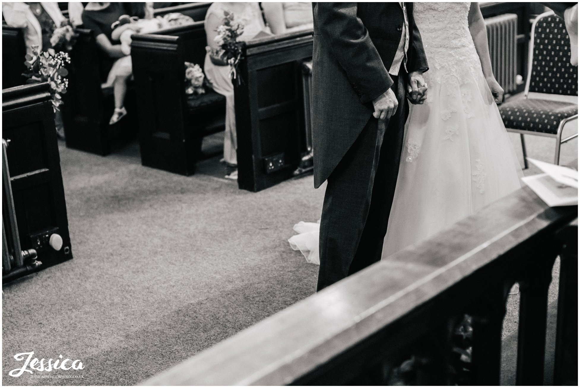 bride & groom hold hands during their ceremony at st chad's church in farndon, chester