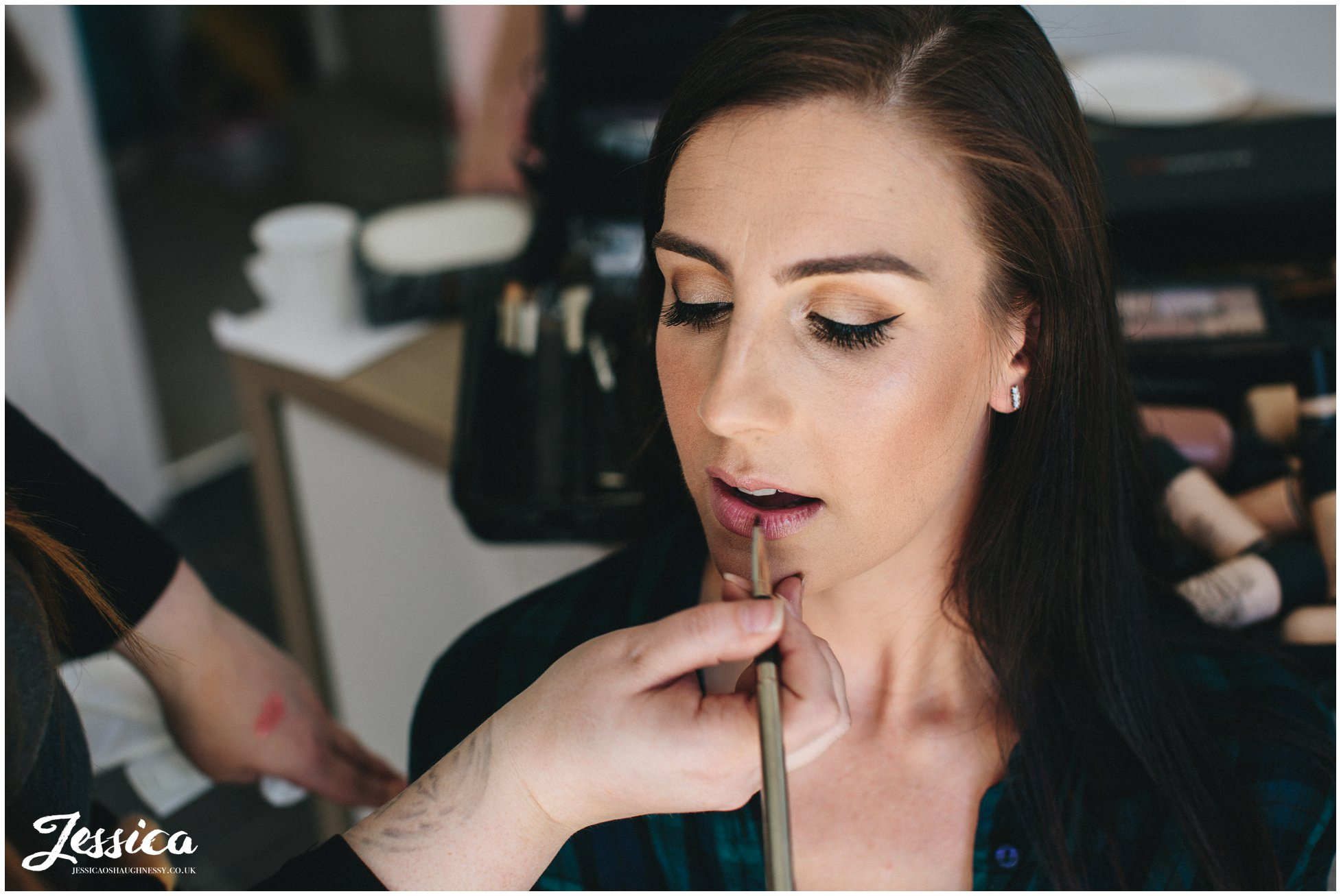 The bride having lipstick applied for her wedding day