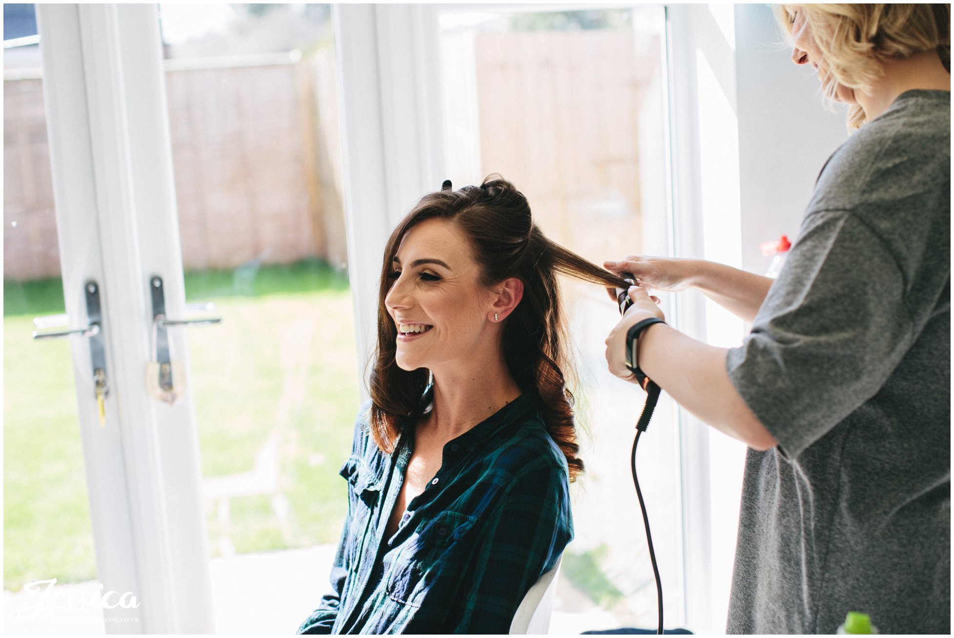 bride has her hair curled ready for her wedding day