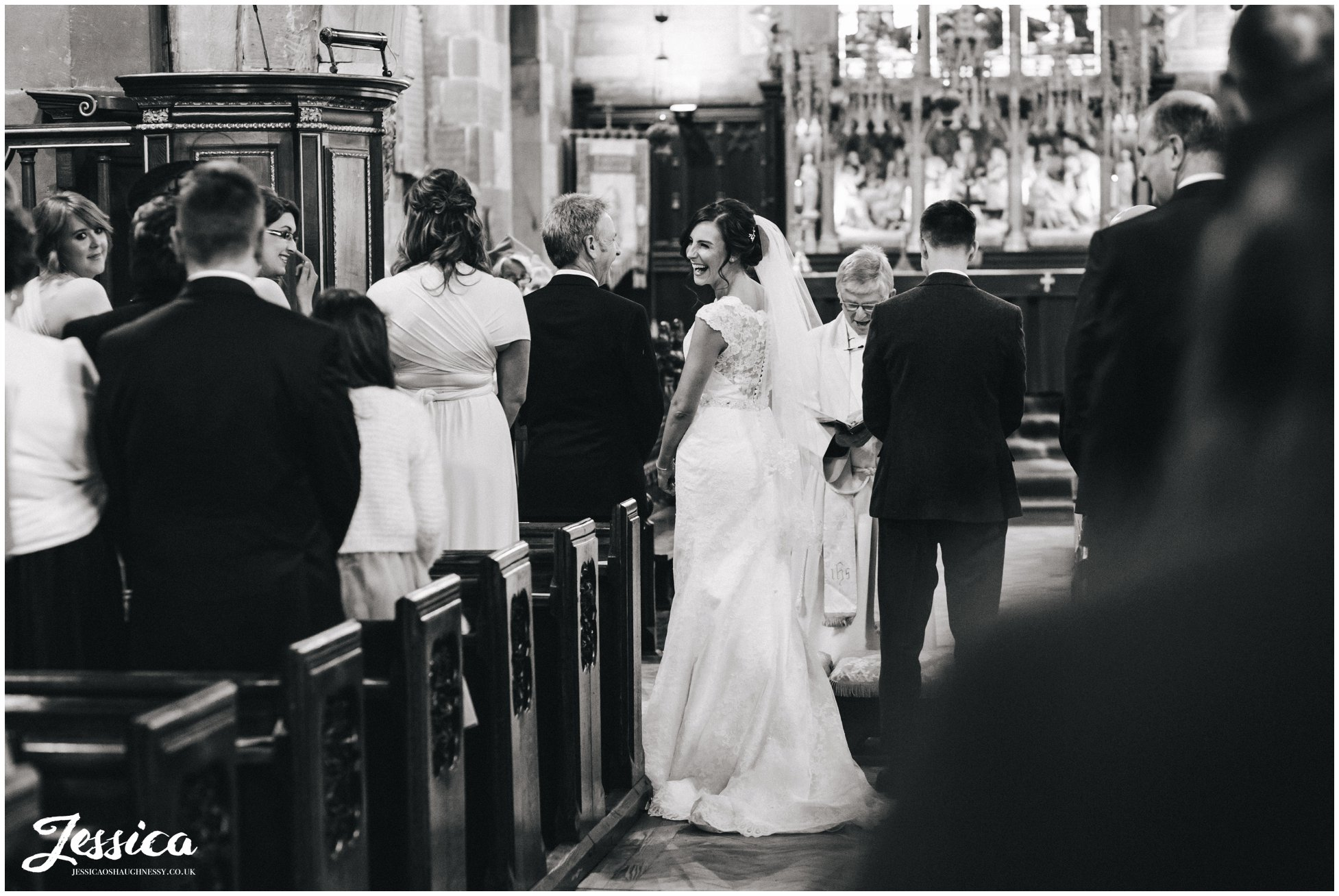 black and white photograph of the bride laughing during the ceremony at st deiniols church, north wales