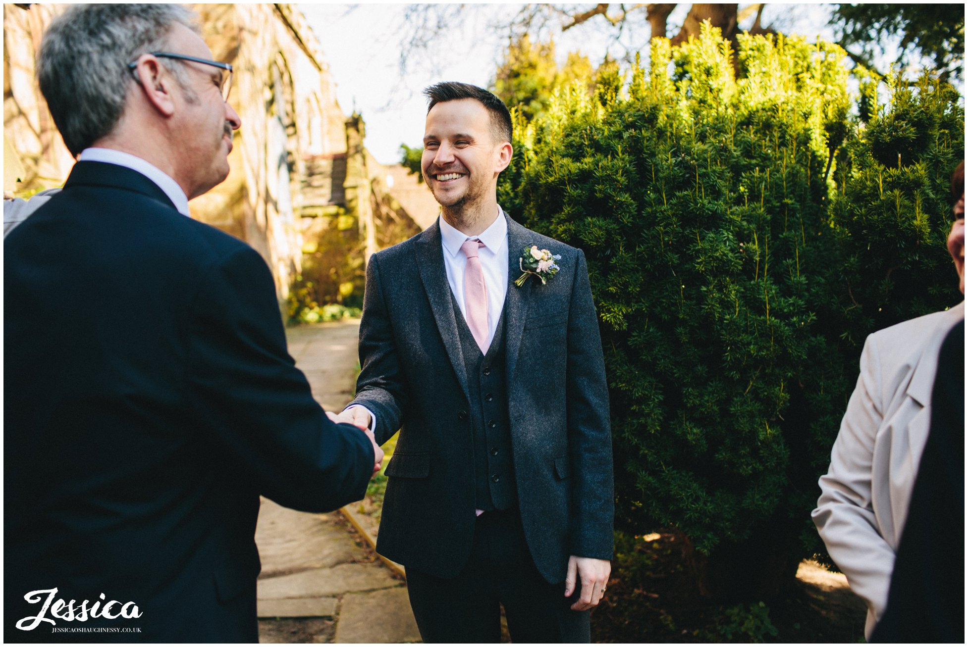 guest shakes the grooms hand after he gets married in hawarden
