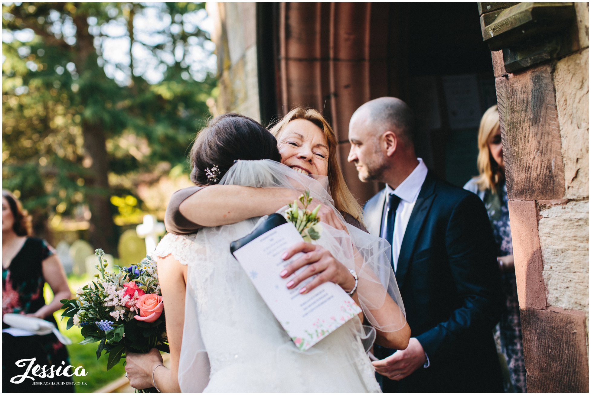 guest embraces the bride after the service at st deiniols church in north wales