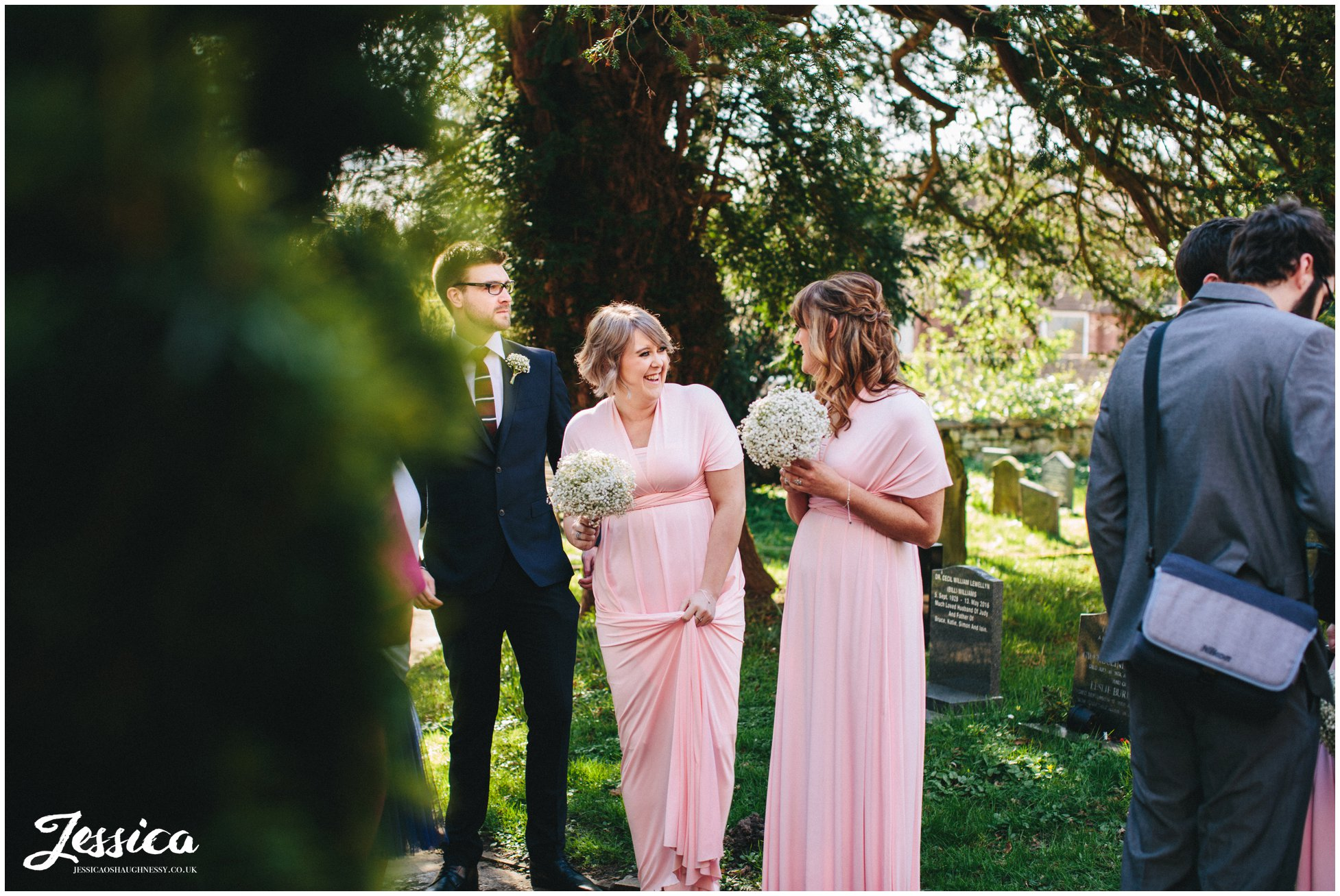 bridesmaids laugh whilst stood outside st deiniols church in hawarden