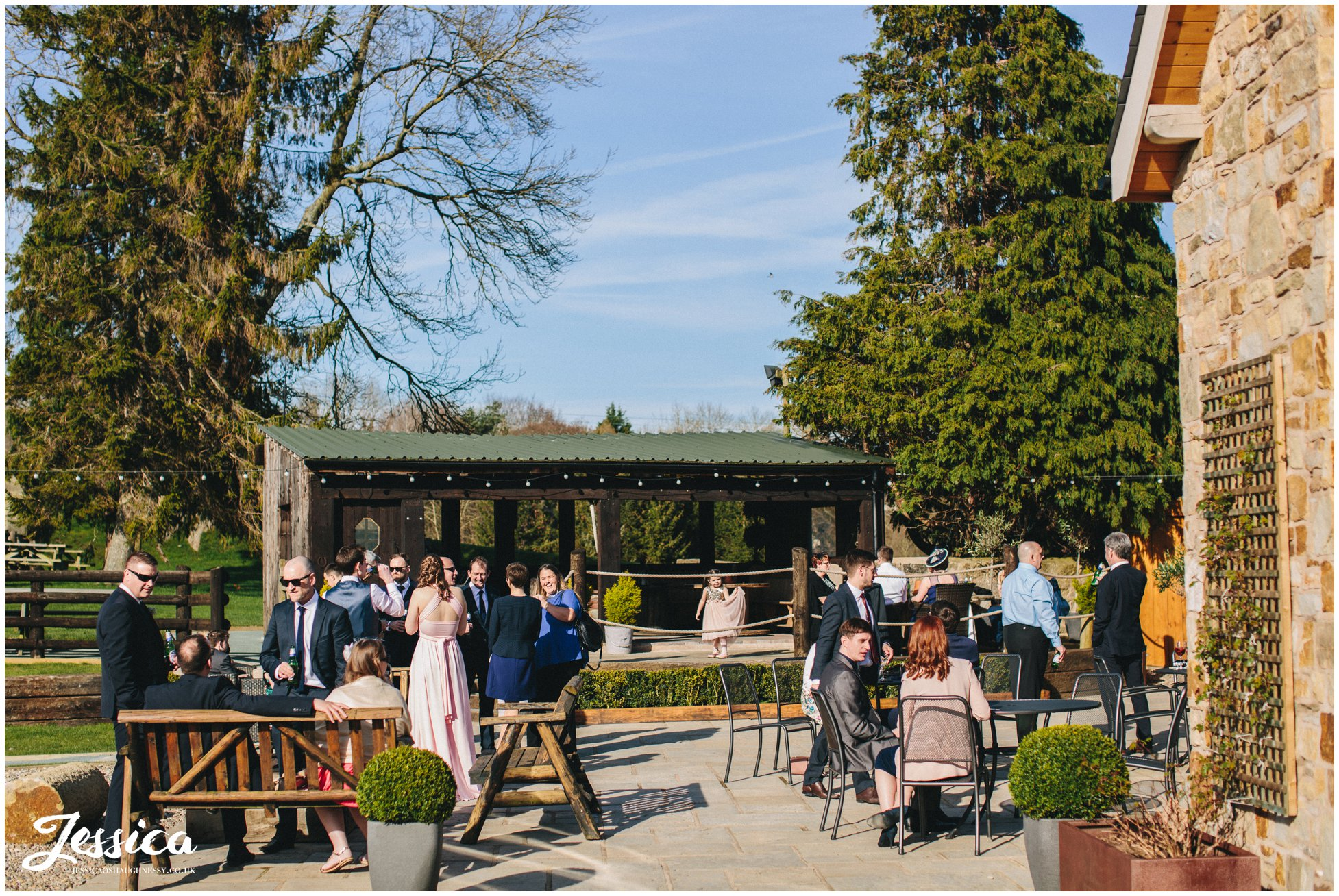 guests stood in the sunshine at the wedding reception in north wales