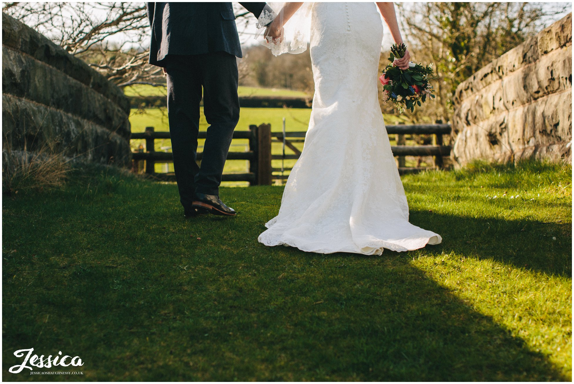 bride and groom hold hands walking over the bridge at tower hill barns