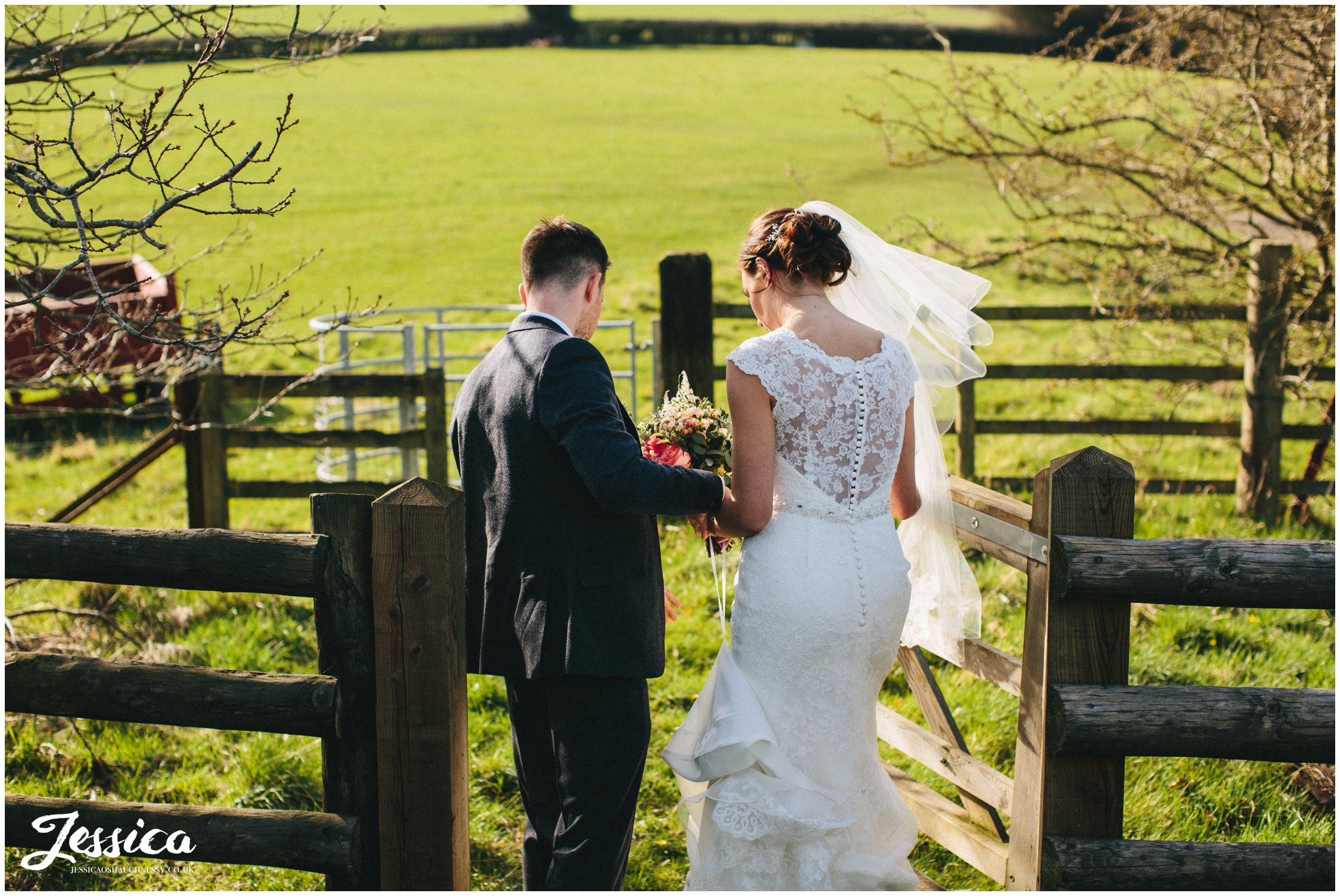 groom helps his bride through wooden gate on their wedding day - north wales wedding photographer
