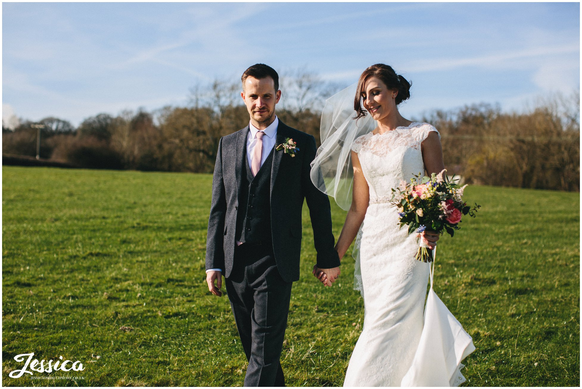 husband & wife walk in the sun at their wedding in north wales